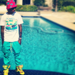 Lil Twist Rocks A Colorful Pink Dolphin Tee-Shirt, All Over Ghost Bucket Hat & Jeremy Scott Bear Shoes