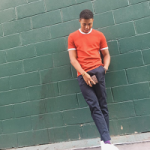 Diggy Simmons Outfitted In A Neil Barrett Contrast Edge Knit Tee-Shirt, Acne Studios Max Satin Slim-Fit Cotton Chinos & Paul Smith Sneakers