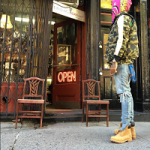 Dave East Outfitted In A Bape Multi Color Shark Hoodie, Wind Stopper 1st Camo Down Vest & Timberland 6″ Classic Boots