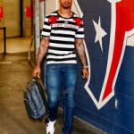 NFL Style: Jaelen Strong Wears A Gucci Tee-Shirt With Parrots Embroidery, Balmain Slim Fit Biker Jeans & Gucci Embroidered Low-Top Sneakers