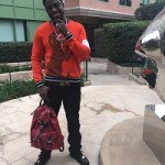 Gucci Mane Wears A Paul Smith Dinosaur Intarsia Sweater & Carries A Giuseppe Zanotti Black Zip Trim Backpack