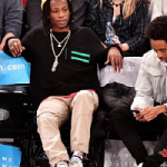 Joey Bada$$ Dressed In A Raf Simons Oversized Striped Wool Sweater & Balenciaga Men's Triple S Sneakers