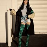Monica Arnold Wears A Raf Simons American Letterman Jacket And Balenciaga Green Floral Lace Over The Knee Boots
