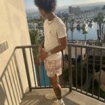 Mikey Williams Styles In A Burberry Logo Print Tee-Shirt, Ryoko Rain Paisley Mocha Shorts And Gucci Rhyton Leather Sneakers